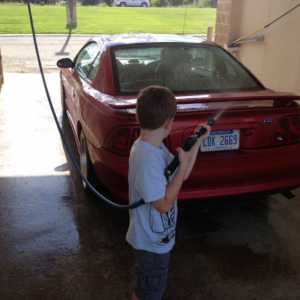My son giving her a bath. He's as bad as me about cars.